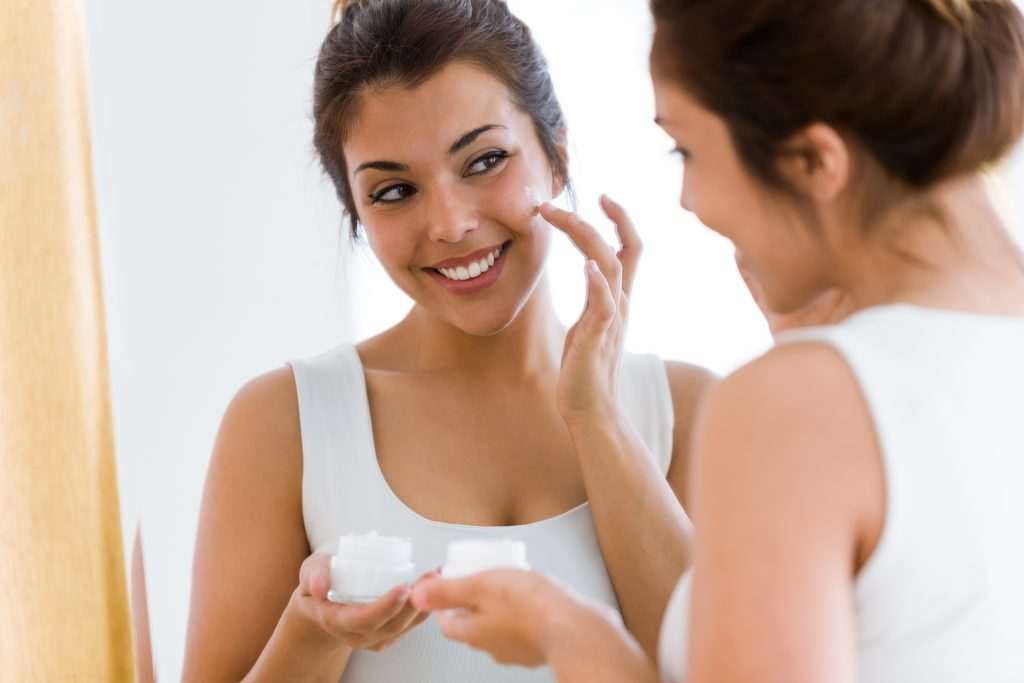 women applying moisturizer on her skin